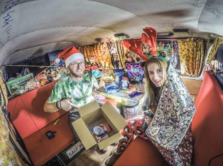 Pareja de Bloggers dentro de una furgoneta vestidos celebrando la navidad