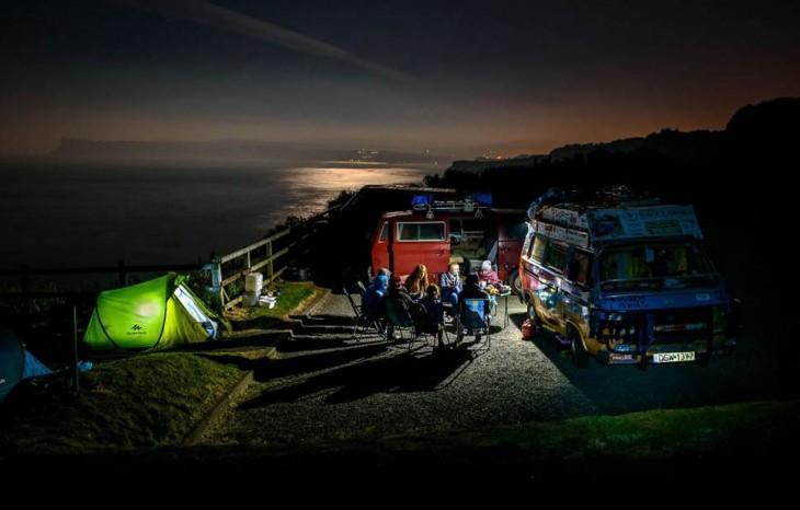 Personas en la noche cerca de montañas con casas de campañas y furgonetas