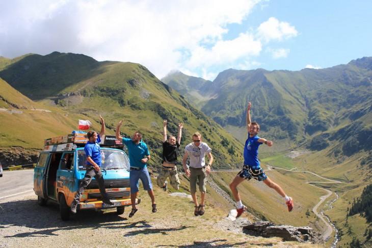 chicos saltando frente a la furgoneta que ha viajado más de 50 países