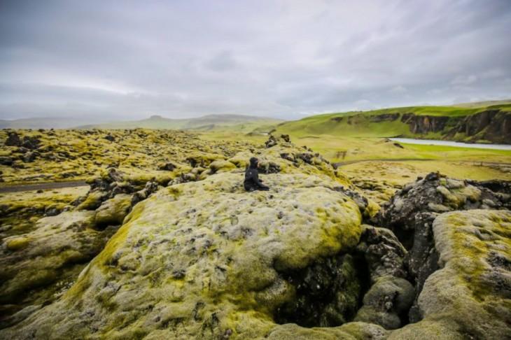 Persona sentada sobre los campos verdes en Islandia
