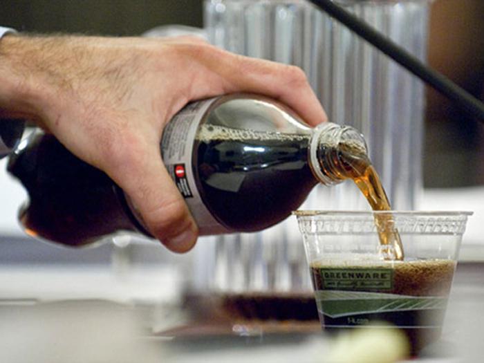 Persona sirviendo refresco de cola en un vaso