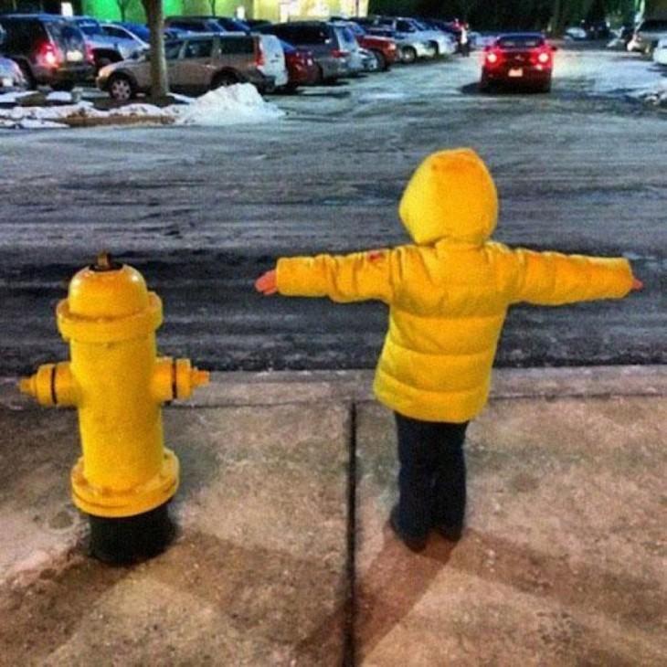 niño con una chamarra simulando ser una bomba de agua en una calle