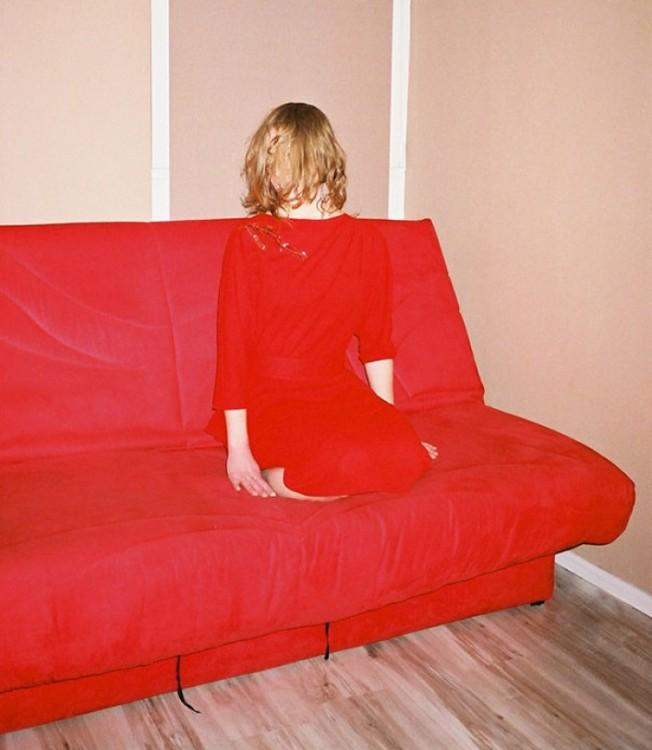 chica de rojo camuflajeada sobre un sillón el mismo color