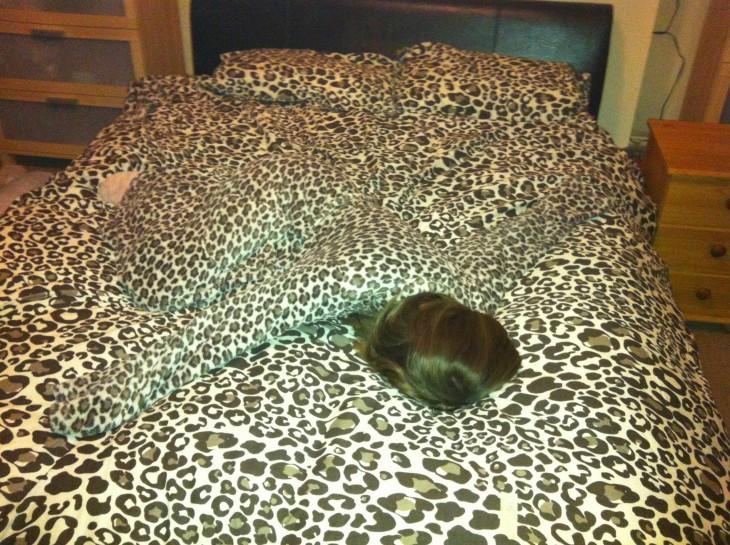 mujer clamuflajeada con la colcha de leopardo de una cama
