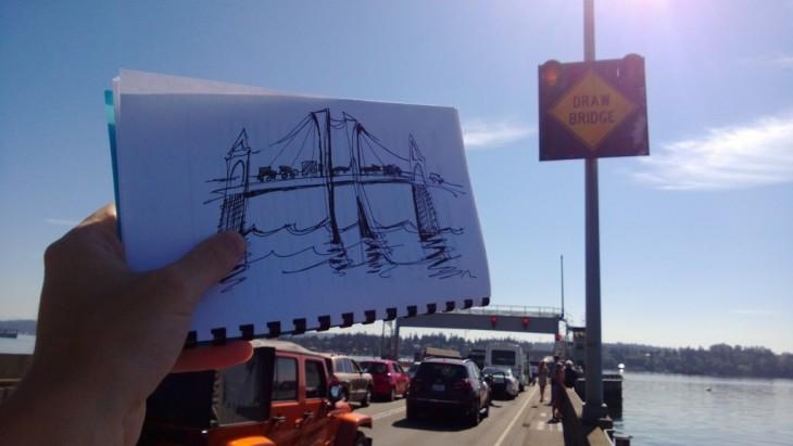 fotografía de una persona mostrando el dibujo de un puente mientras está en un embotellamiento