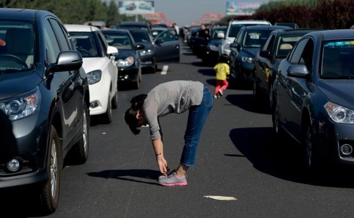 Mujer atorada en el tráfico haciendo ejercicio en medio de los coches