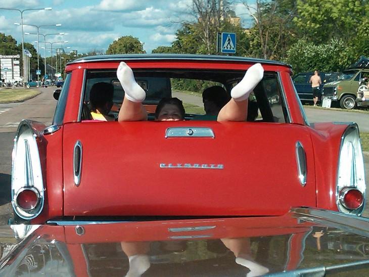Niño acostado en la parte trasera de una camioneta con los pies hacia afuera