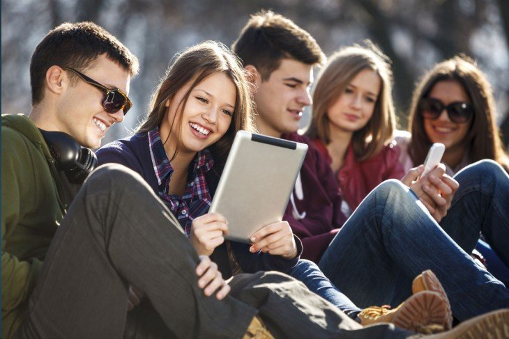 Grupo de 5 chicos con tablets y celulares en sus manos