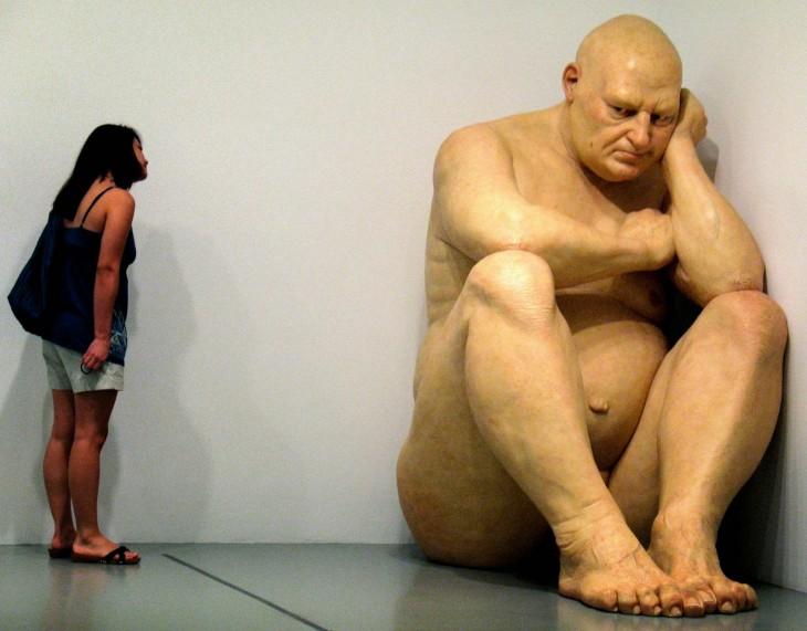 Escultura gigante de un hombre sentado en la esquina de un cuarto