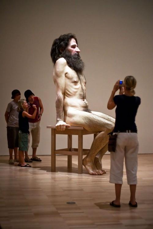 Escultura gigante de un hombre sentado sobre un banco