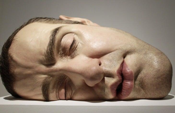 Escultura gigante y realista de la cara de un hombre