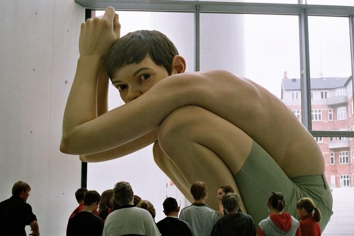 Escultura gigante de un chico sentado a cargo del artista Ron Mueck