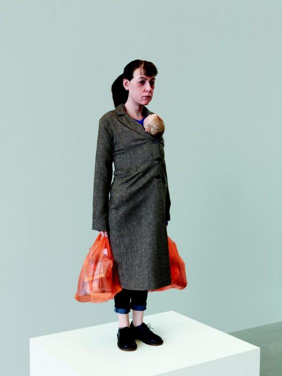 Escultura gigante de una mujer con un bebé sobre su pecho y dos bolsas de mandado