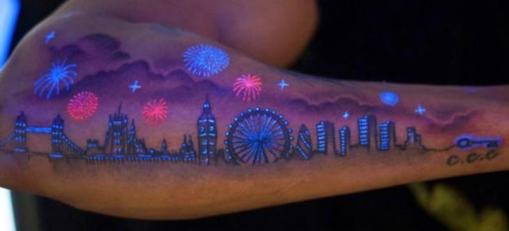 Tatuaje ultravioleta en un brazo con el diseño de una ciudad con edificios y pirotecnia