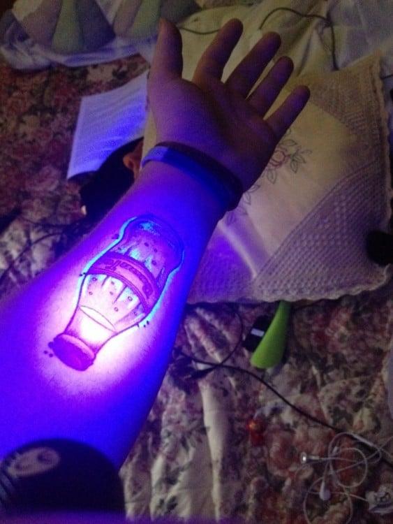 Tatuaje ultravioleta en un brazo con el diseño de una botella de vidrio