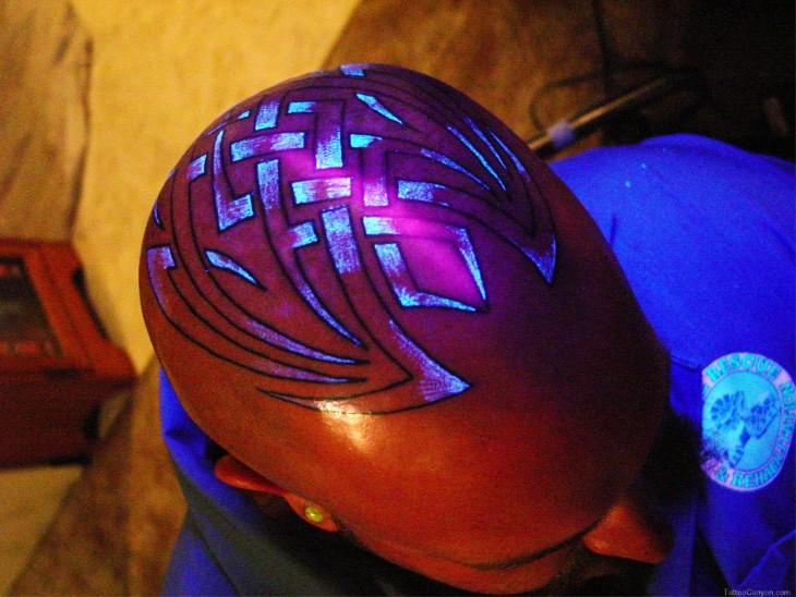 cabeza de un hombre con un tatuaje ultravioleta con un diseño tribal