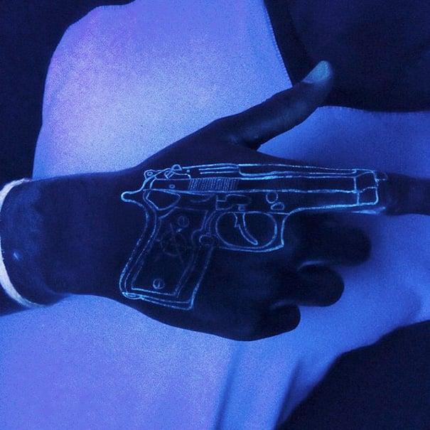 tatuaje que brilla en la luz negra del diseño de una pistola en la mano