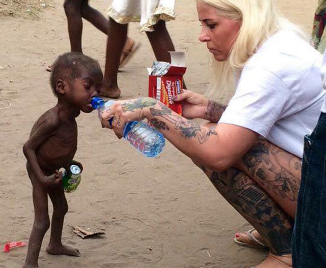activista dándole agua a niño abandonado en Nigeria