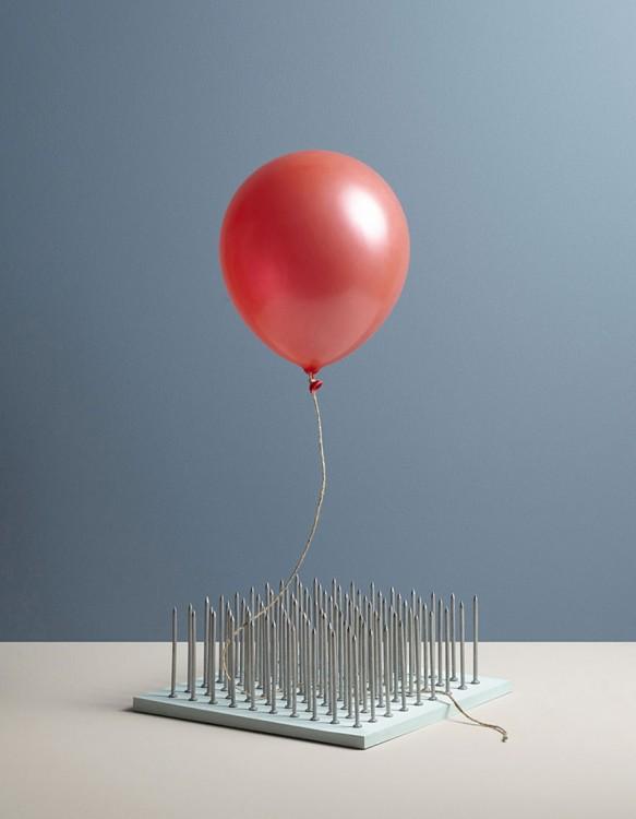 globo rojo sobre un cuadro lleno de clavos filosos