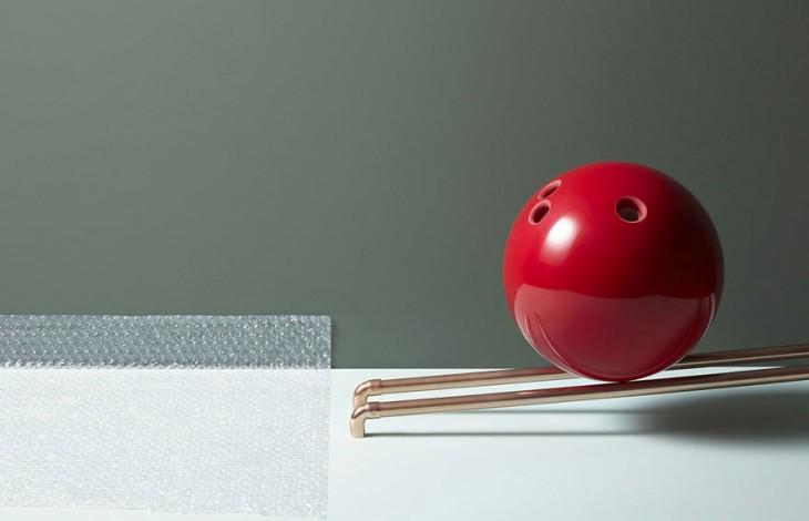 Fotografía de una bola de boliche roja sobre dos tubos a punto de caer