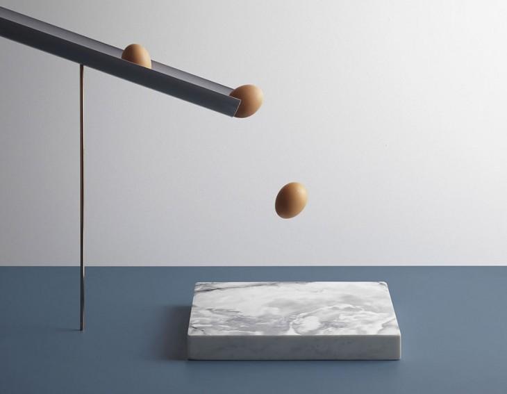 Fotografía de unos huevos a punto de caer sobre un cuadro de mármol