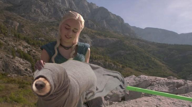Daenerys Targaryen de Game of Thrones acariciando a un perro que tiene sentado entre las piernas