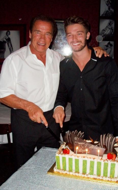 Arnold Schwarzenegge y Patrick partiendo un pastel