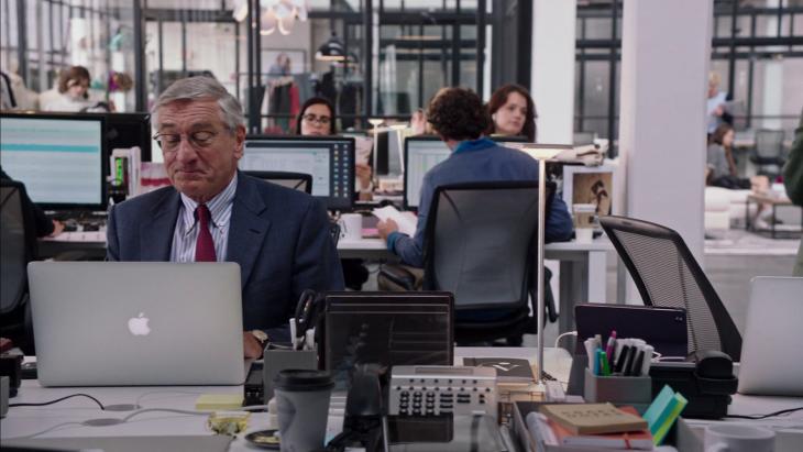 Jefe sentado con los empleados frente a una laptop