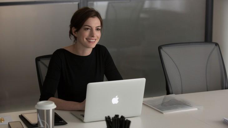 Actriz Anne Hathaway sentada sobre un escritorio frente a una laptop