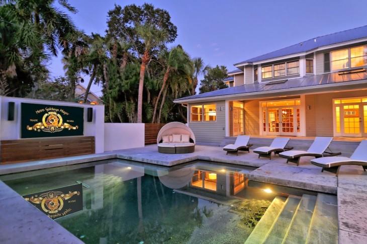 pantalla de cine frente a una piscina en una mansión