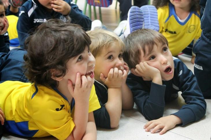 Niños acostado en el suelo escuchando asombrados