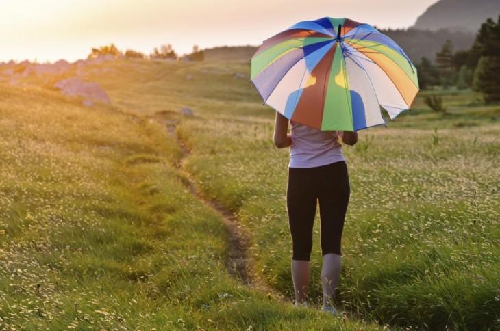 chica parada sobre un césped con una sombrilla de colores