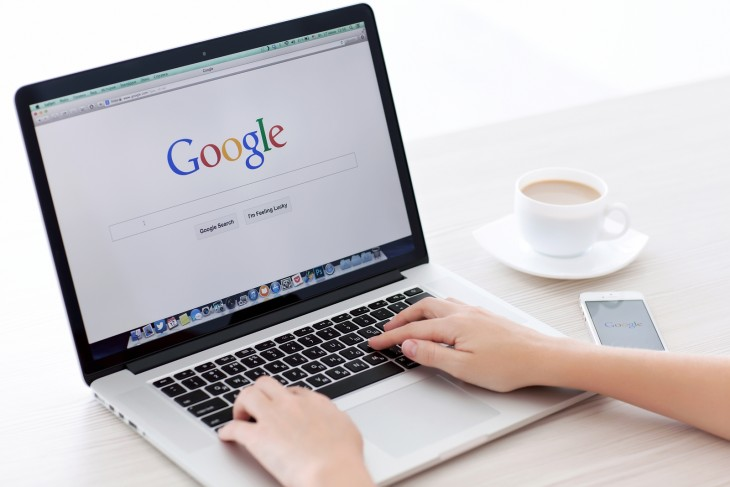 manos de una persona sobre una laptop a punto de hacer una búsqueda en Google