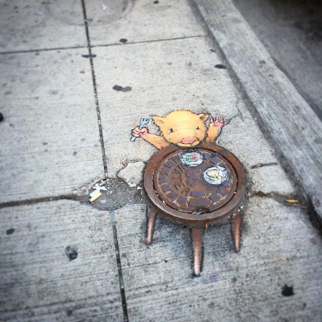 desenho de um rato feito com giz interagindo com um esgoto de um banco