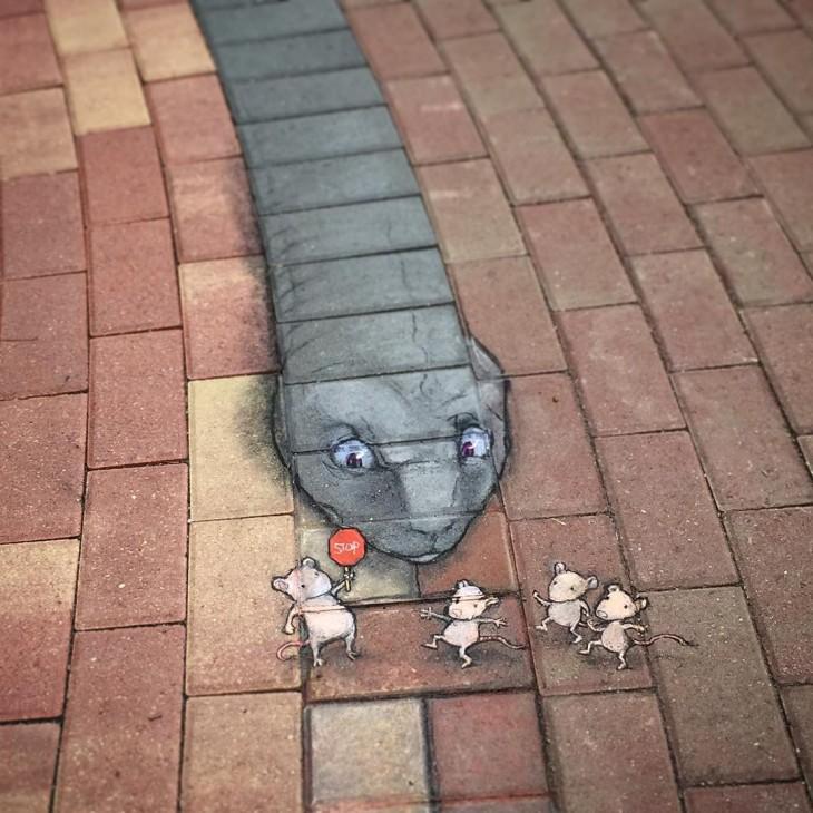 dibujos hechos con tiza en una banqueta que simula ser una serpiente persiguiendo cuatro ratones