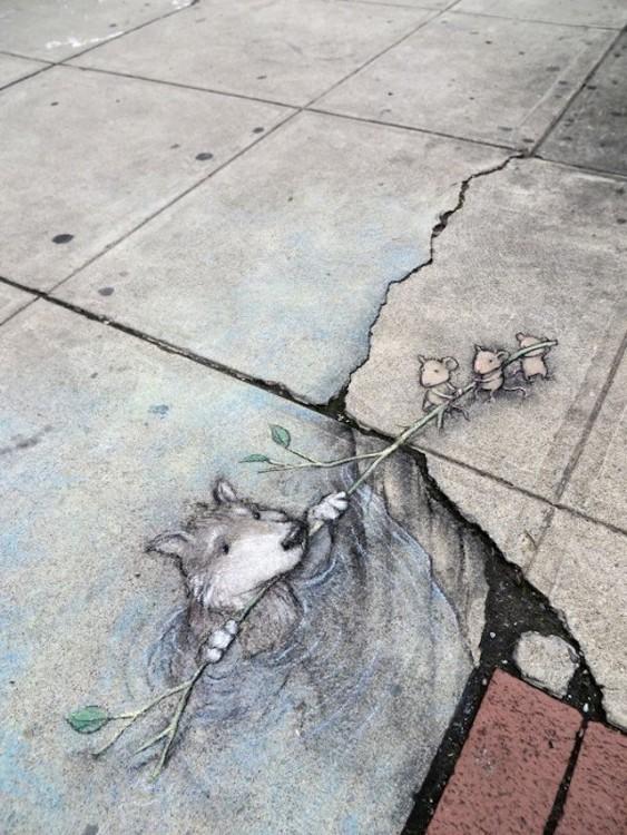 obra de arte en el suelo de una calle donde un osito está siendo salvado por tres ratones