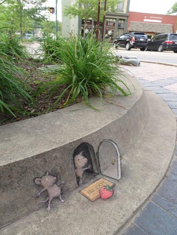 David Zinn creo un dibujo de tiza de un ratón saliendo de una casa mientras otro se le esconde