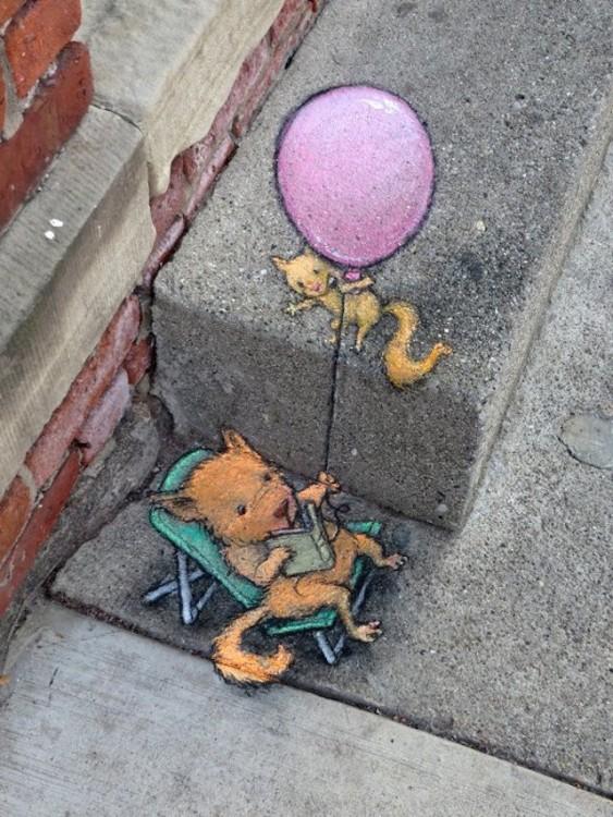dibujo en tiza de un gatito leyendo con un globo en su mano