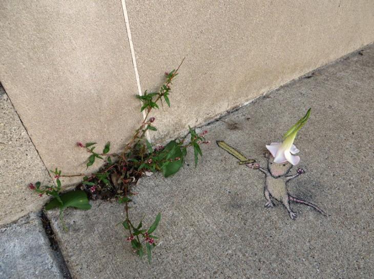 Dibujo con tiza de un ratón interactuando con unas hojas que salen del cemento
