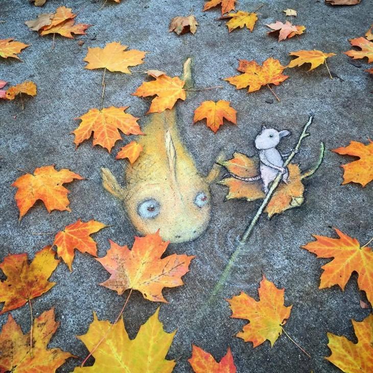 David Zinn creo una obra de arte en el suelo de un pez con un ratón interactuando con hojas secas en el suelo