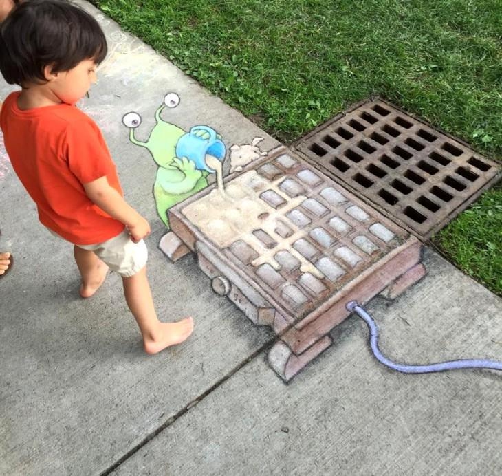 Obra de arte urbano dibujado con tiza interactuando con una alcantarilla