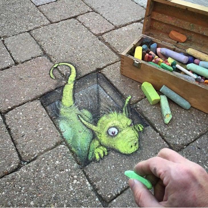 David Zinn dibujo con tiza en una calle un dibujo de un dragón saliendo de una banqueta