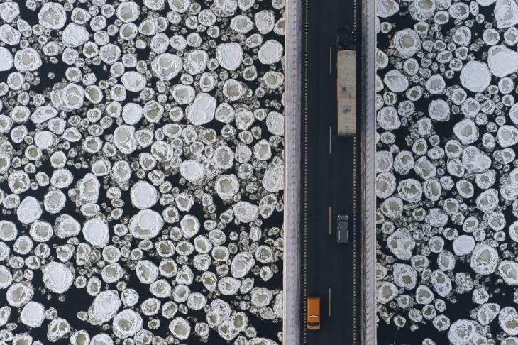 fotografía muestra carros que recorren un puente sobre un mar congelado
