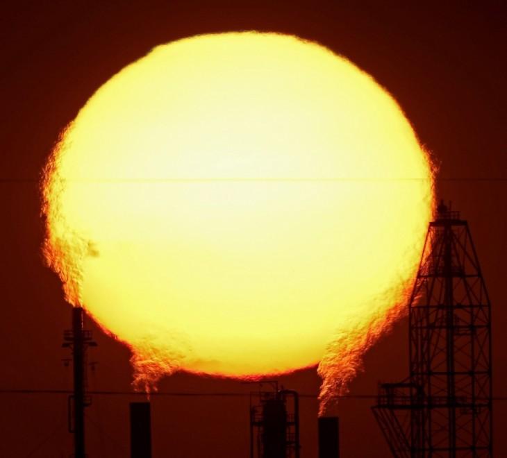 Fotografía del sol visto entre las fábricas