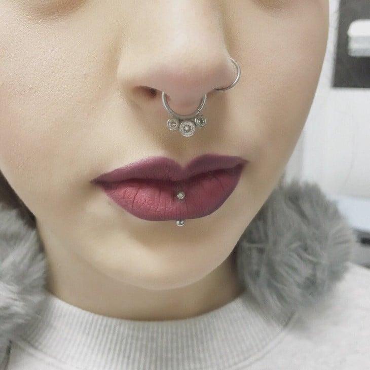 cara de una chica con piercings en la nariz y en un labio