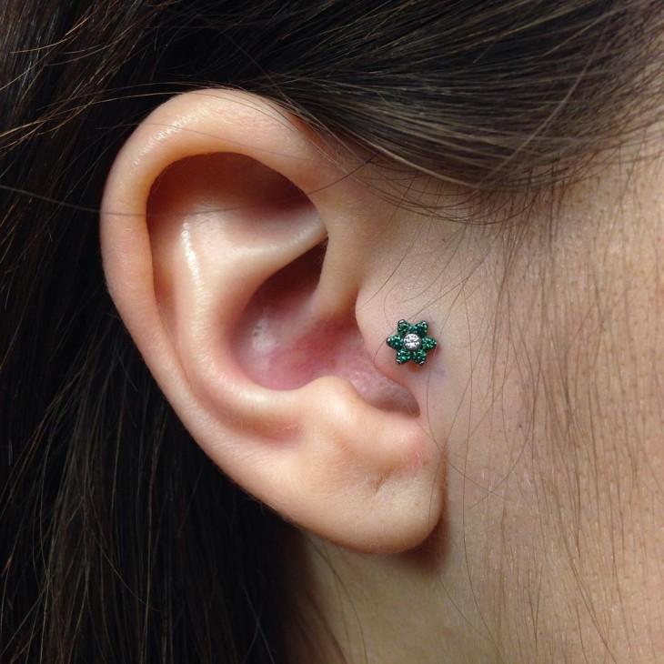 piercing en forma de flor en color verde cerca del oído