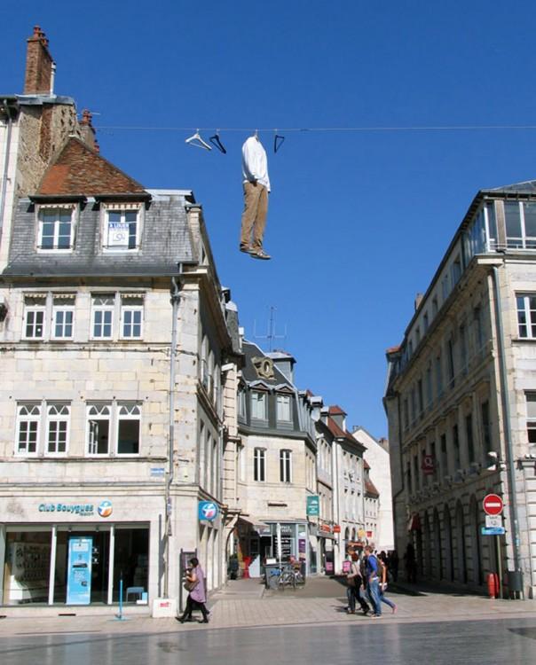 escultura en forma de un cuerpo real colgado entre dos edificios
