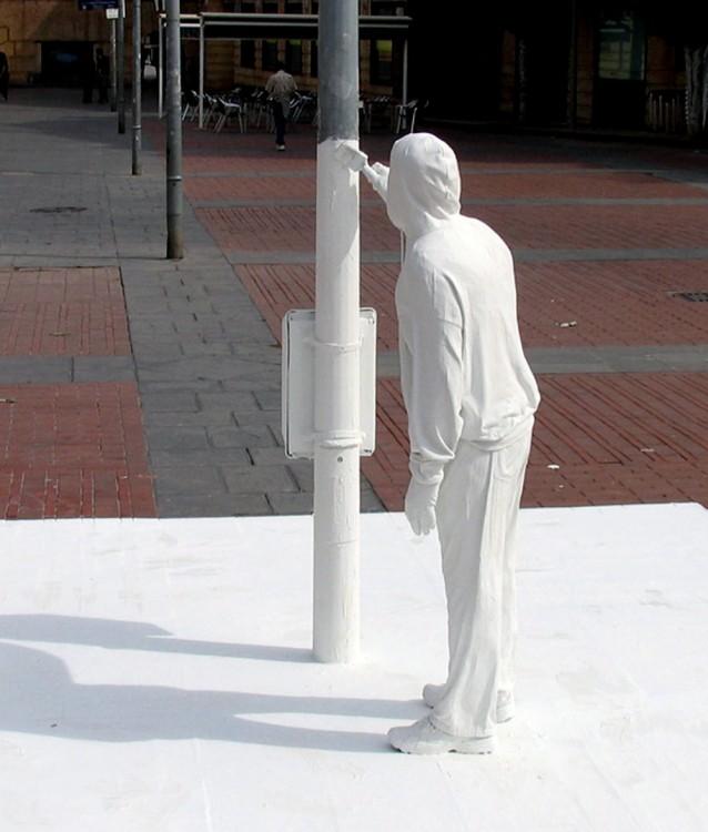 Impresionantes escultura callejera de una persona pintando un poste de color blanco