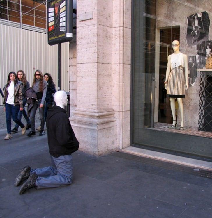 escultura de una persona real hincada frente un aparador