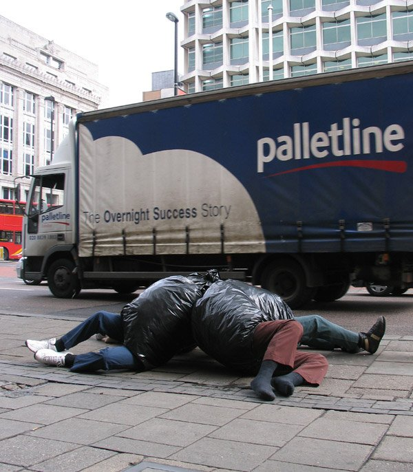 Esculturas realistas en el piso con unas bolsas de basura en las calles